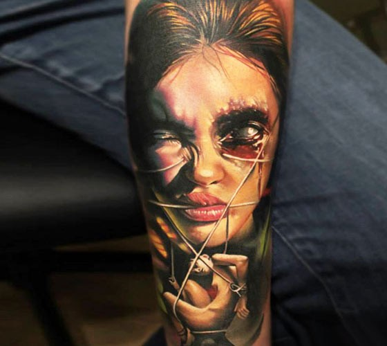 Colored horror style colored forearm tattoo of monster woman