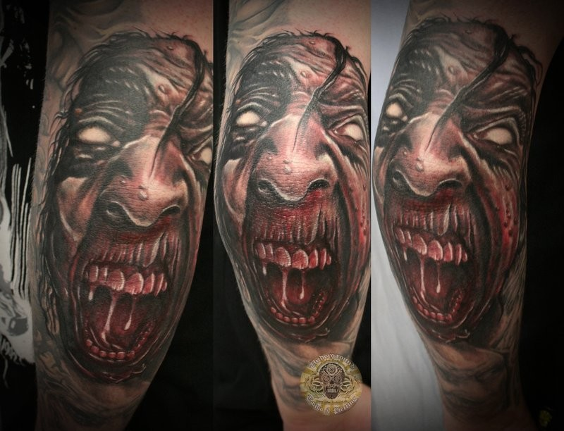 Colored horror style creepy looking arm tattoo of demonic face