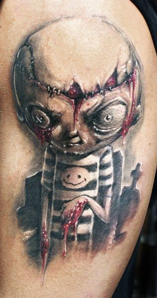 Colored horror style creepy looking bloody doll tattoo on shoulder