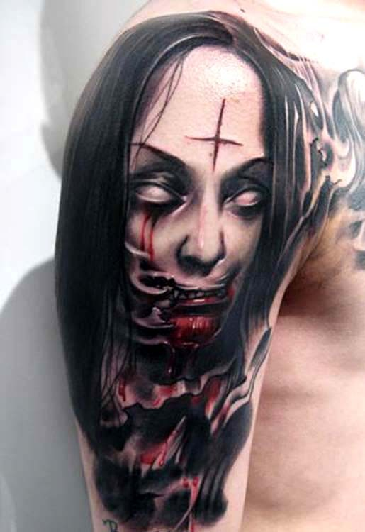 Colored horror style creepy looking bloody woman face tattoo on shoulder