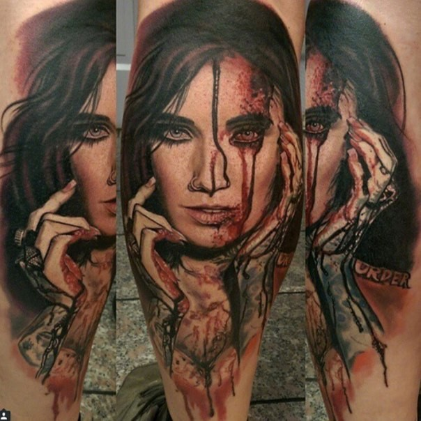 Colored horror style creepy looking bloody woman face tattoo on leg