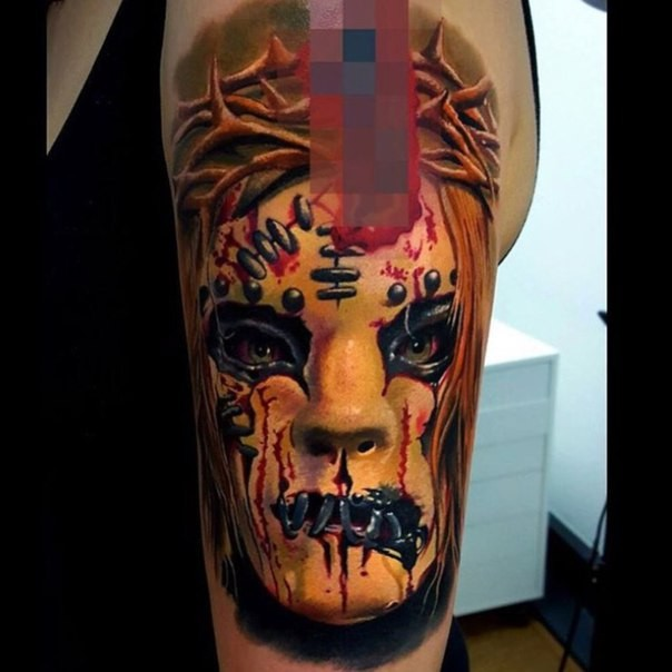 Colored horror style creepy looking face with vine tattoo on shoulder