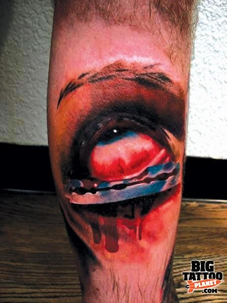 Colored horror style creepy looking leg tattoo of eye with razor