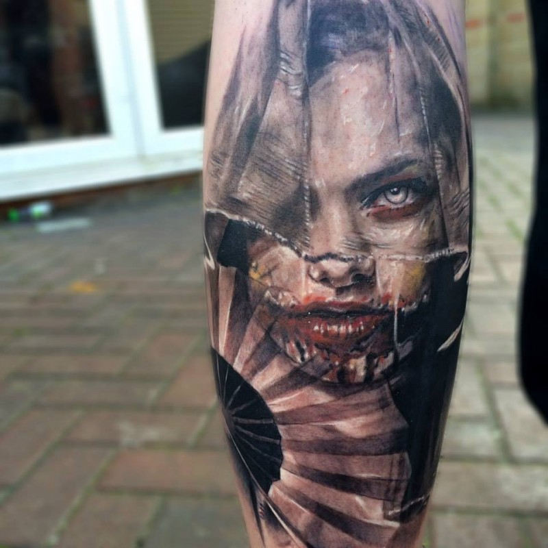 Colored horror style creepy looking leg tattoo of woman face