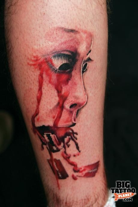 Colored horror style creepy looking leg tattoo of bloody geisha face
