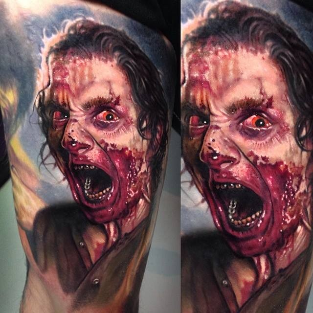Colored horror style creepy looking man portrait tattoo on thigh