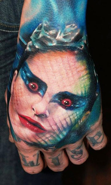 Colored horror style creepy woman face tattoo on hand