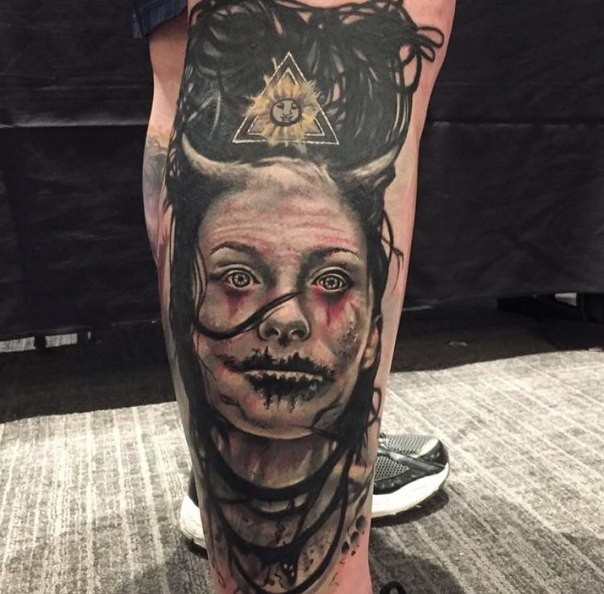 Colored horror style interesting looking leg tattoo of devil woman with horns and emblem