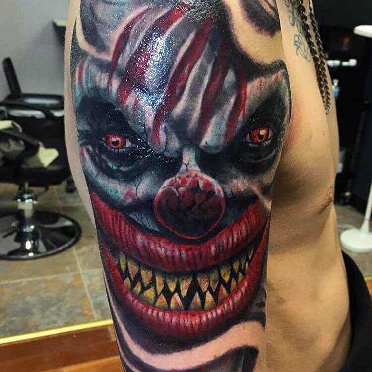 Colored horror style large creepy clown demon face tattoo on shoulder