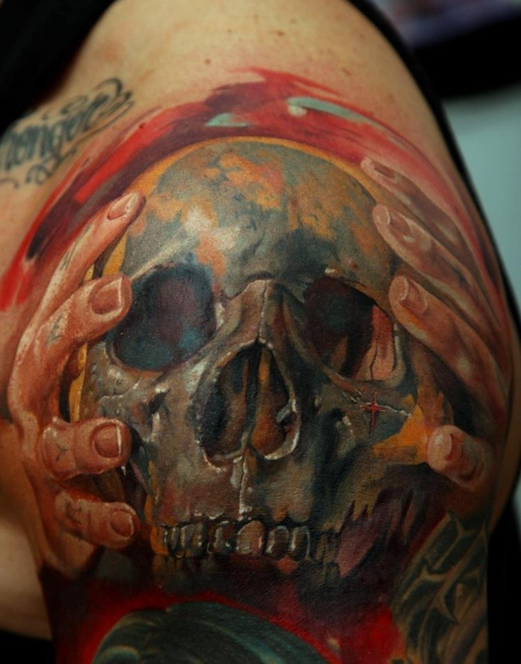 Colored horror style large shoulder tattoo of hands holding human skull
