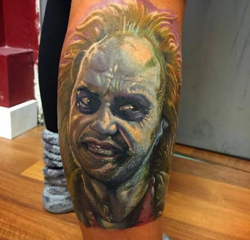 Colored horror style realistic looking leg tattoo of evil monster portrait