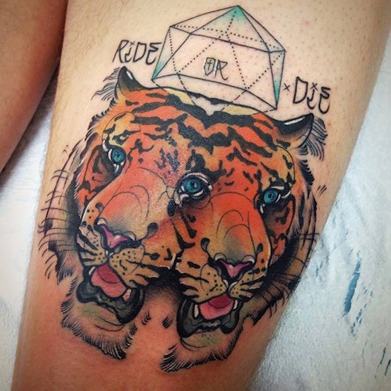 Colored illustrative style thigh tattoo of tiger heads with ornaments and lettering