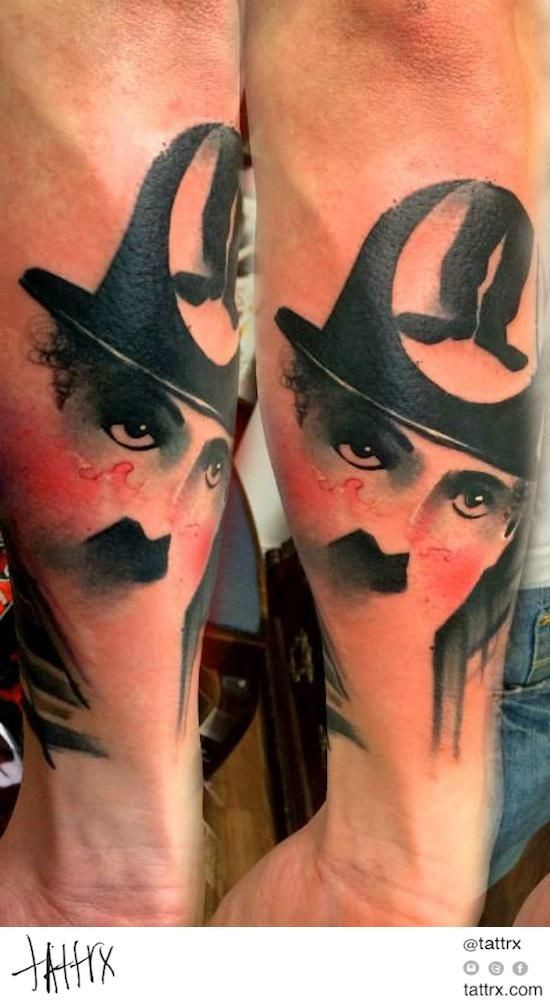 Colored interesting looking arm tattoo of Charlie Chaplin portrait