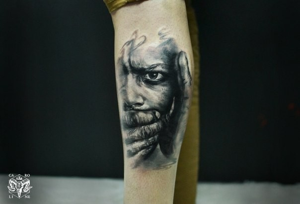 Colored leg tattoo of terrifying human face