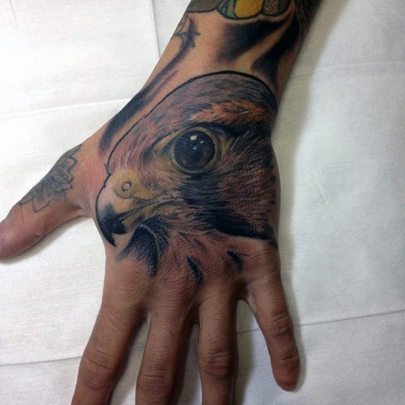 Colored natural looking small hand tattoo of eagle head