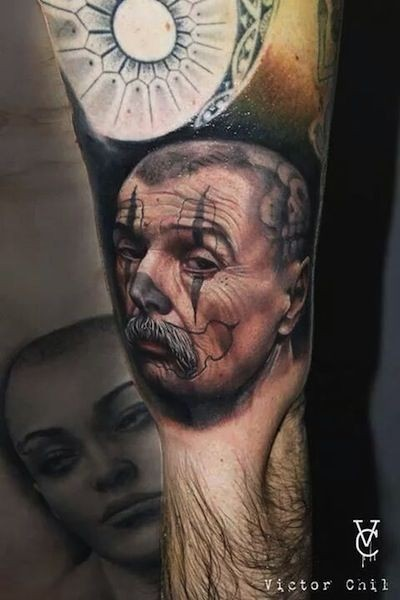 Colored realism style biceps tattoo of man face with mustache