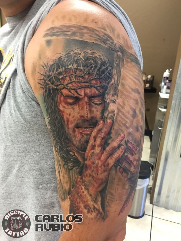 Colored shoulder tattoo of dramatic Jesus with cross