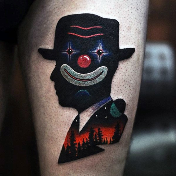 Colored surrealism style thigh tattoo of man silhouette with clown face and night forest