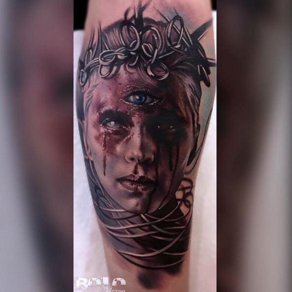 Colored terrifying looking tattoo of woman face with vine