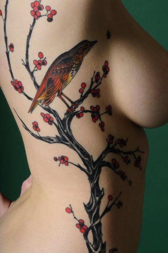 Colorful bird on a tree tattoo