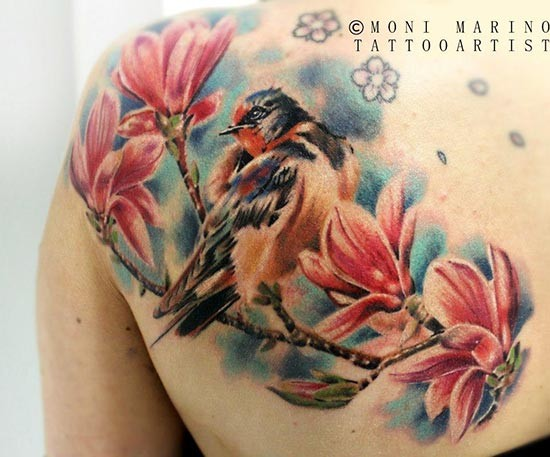 Colorful cartoon style scapular tattoo of bird with blooming tree branch