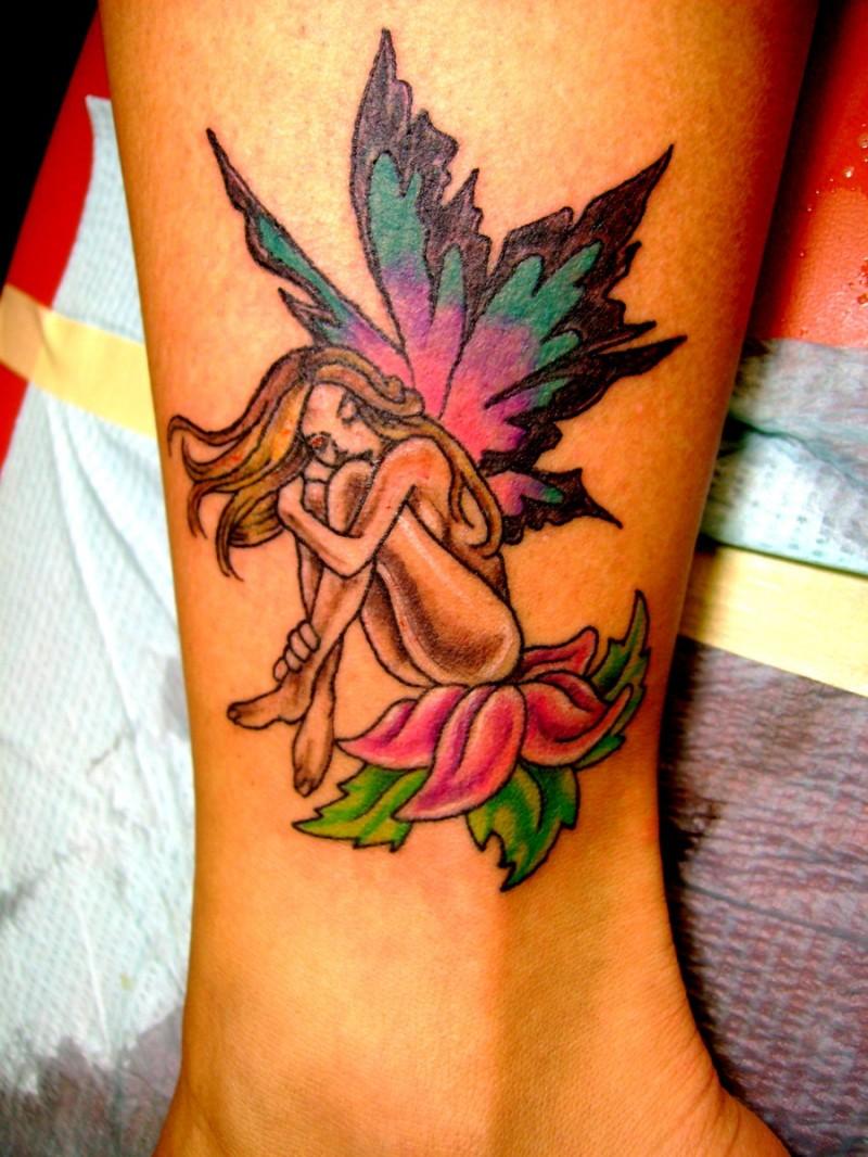 colorato fata seduta sul fiore tatuaggio sulla gamba