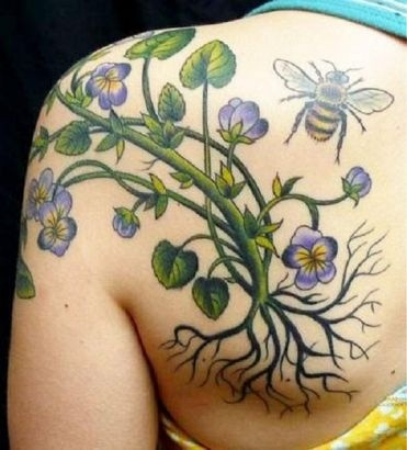 Colorful flower with roots and bee tattoo on shoulder blade