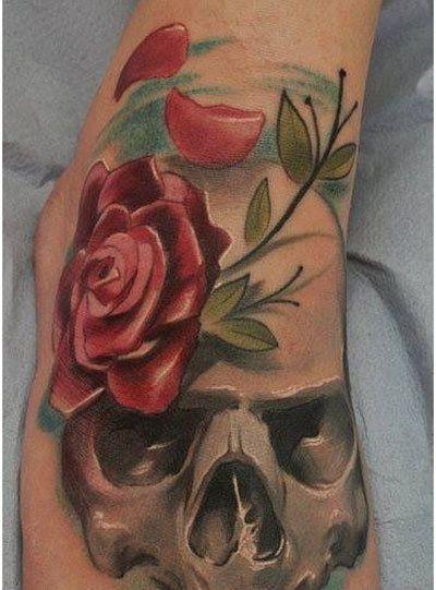 colorato cranio grigio con rosa rossa tatuaggio sul piede