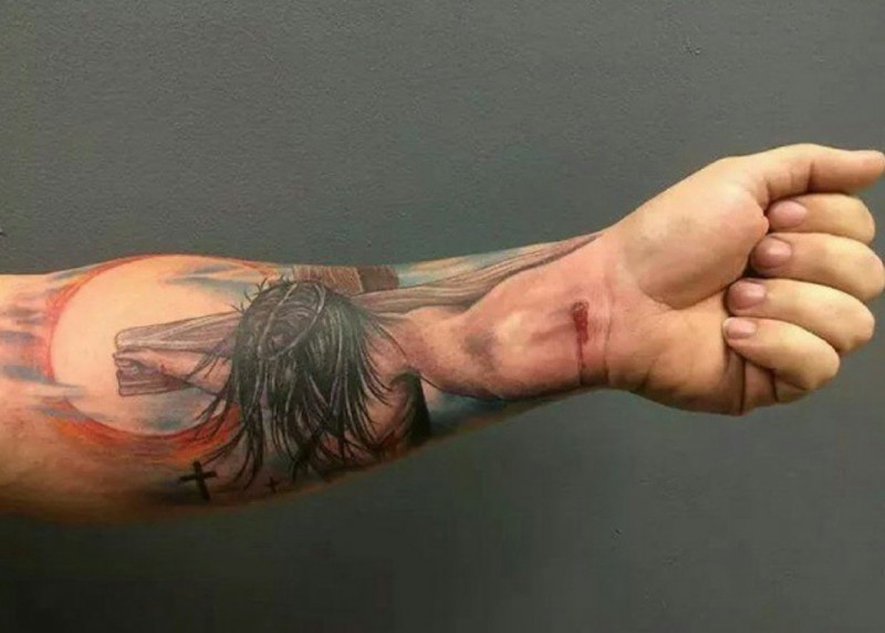 Colorful jesus crucified on a cross forearm tattoo