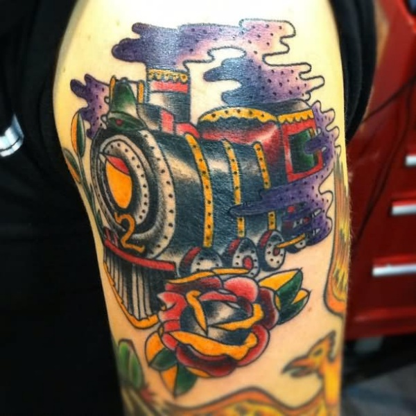 Colorful large upper arm tattoo of train with rose