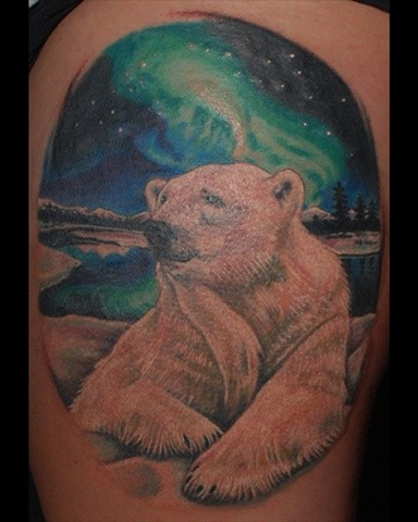 Colorful polar bear with northern lights tattoo on shoulder