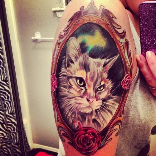Tatuaggio impressionante sul braccio il ritratto del gatto nella cornice