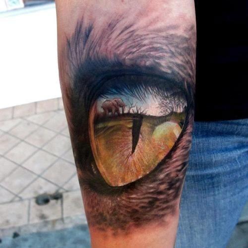 Colorful predator eye tattoo on arm