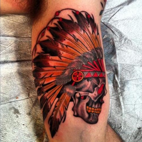 Colorful skull in an indian headdress tattoo on arm