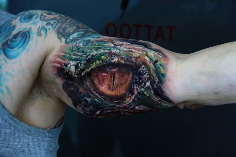 Colorful spooky eye reptile tattoo on arm