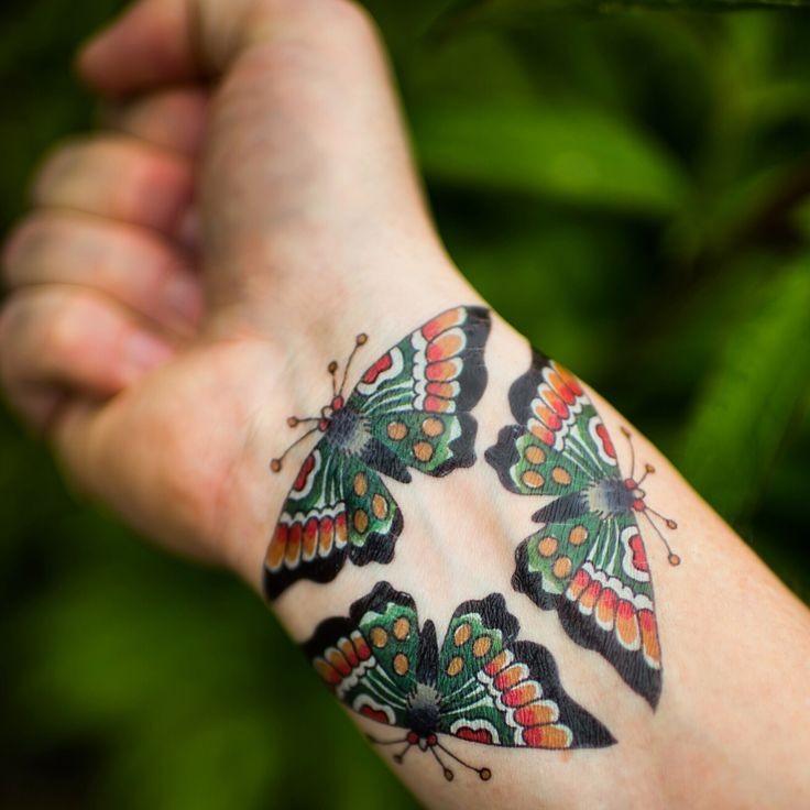 Tatuaggio colorato sul polso tre farfalle formano il triangolo