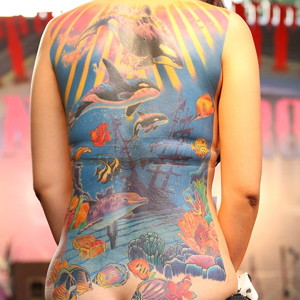Colorful underwater world and killer whales in ocean tattoo on whole back