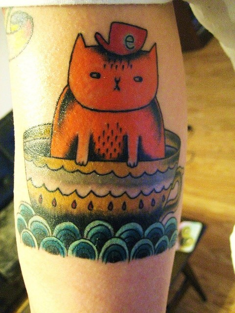 Coloured cat in a teacup tattoo