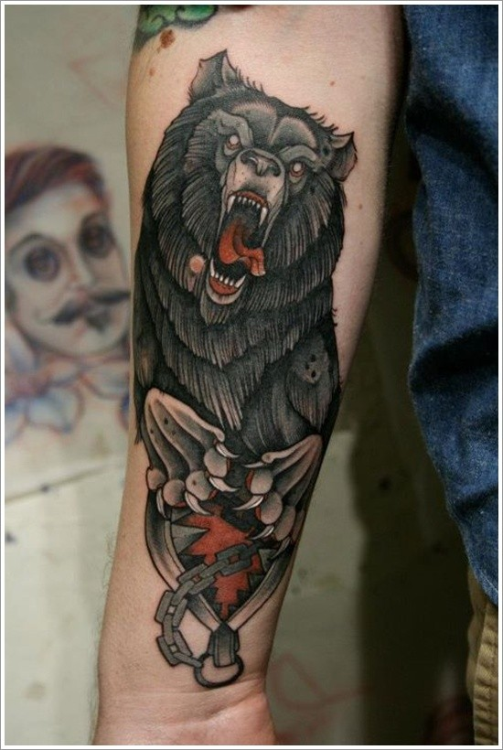 Coloured grizzly bear in a hunting trap forearm tattoo