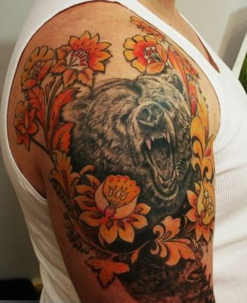 Coloured head of a bear with yellow flowers tattoo on shoulder