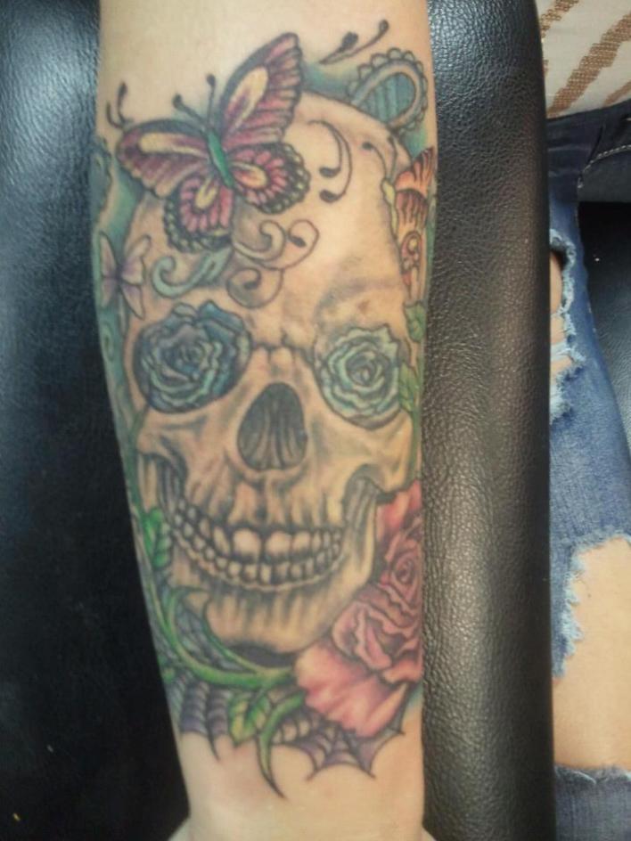 Tatuaggio bellissimo colorato sul braccio il teschio con le rose e la farfalla