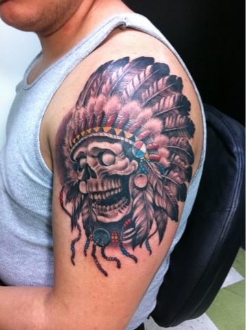 colorato cranio con copricapo indiano tatuaggio sulla spalla