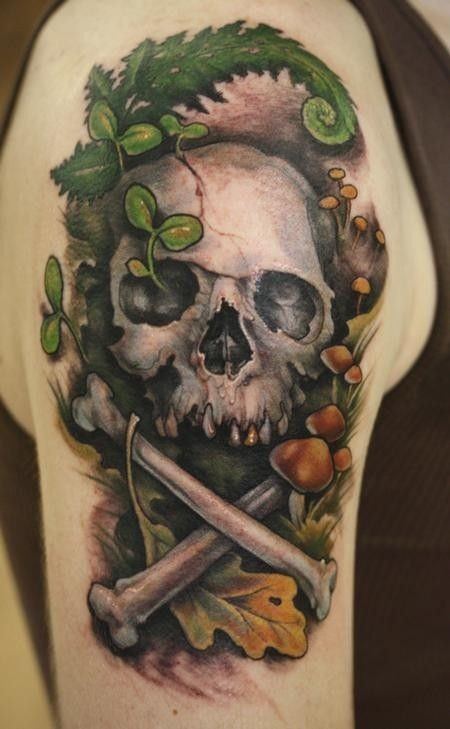 Coloured skull on ground among mushrooms and herbs tattoo on shoulder