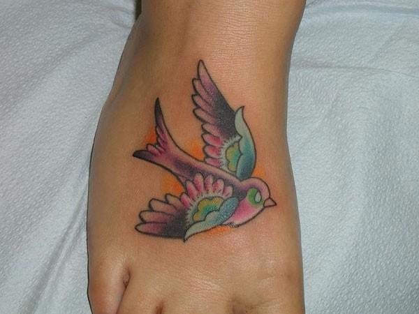 Coloured stylized bird tattoo on foot
