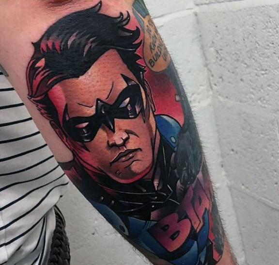 Comic books style colored arm tattoo of Batman and lettering