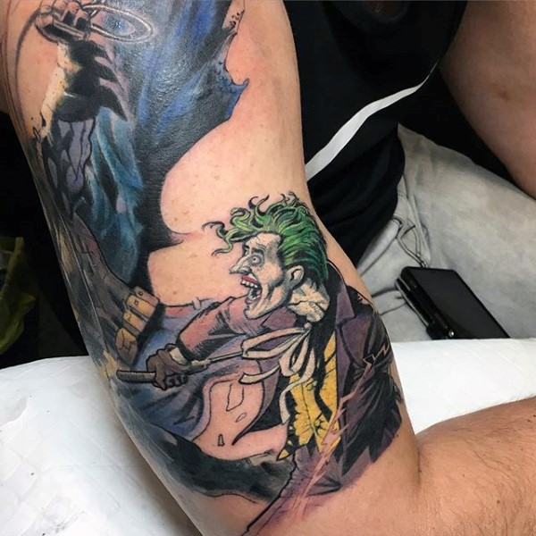 Comic books style colored shoulder and biceps tattoo of Batman and Joker