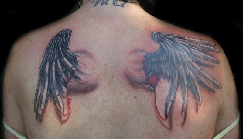 fresco colorato di sangue ali di corvo tatuaggio su parte superiore della schiena