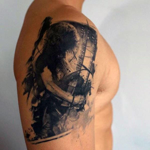 Cool creative black ink upper arm tattoo of rock guitar player