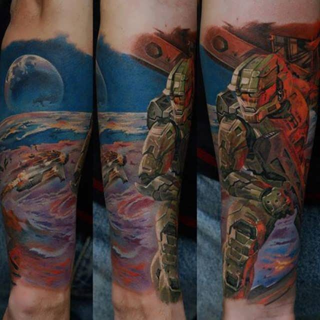 Cool designed and colored Halo video game themed tattoo on forearm with space soldier