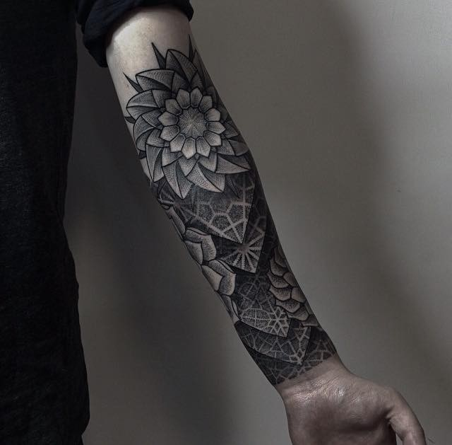 Cool gray-ink tattoo sleeve with abstract flower on forearm
